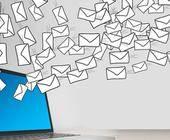 Gezeichnete Mail-Umschläge fliegen aus einem Notebook